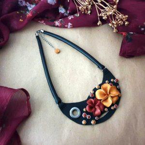 Neobična ogrlica Flower Mini od crne eko kože s cvjetnim uzorkom i metalnim detaljima.