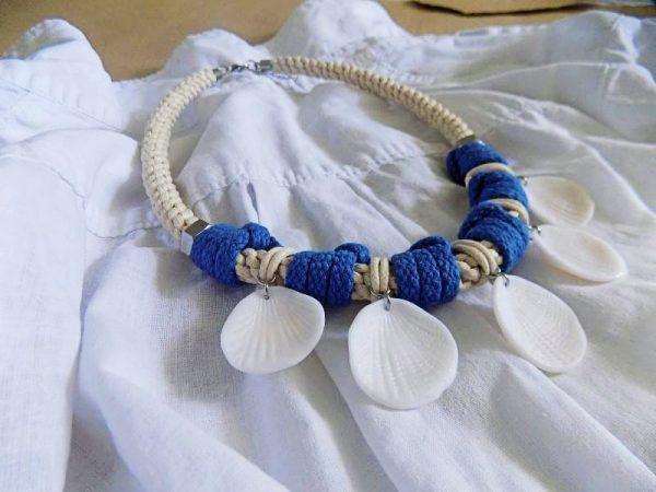 Ogrlica Summer Dancers napravljena je od pletenog užeta prirodne boje i ukrašena dodacima koji podsjećaju na morske školjke